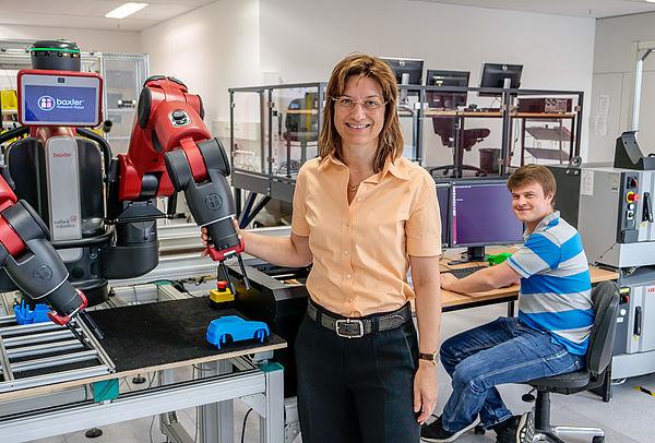 """Prof. Dr. Iris Gräßler und Alexander Pöhler arbeiten mit dem Roboter """"baxter"""" im Smart Automation Laboratory der Universität Paderborn."""