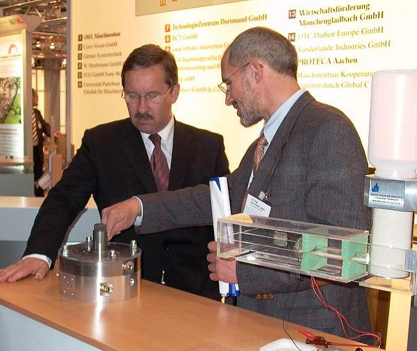 Foto: Minister Schartau (li.) lässt sich von Dr.-Ing. Karl-Peter Jäker, Universität Paderborn, das Prinzip der Flügelzellenpumpe erklären