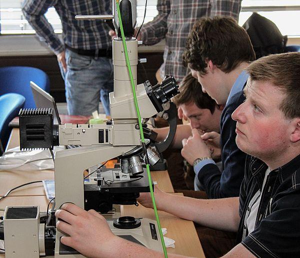 Foto (Universität Paderborn, Department Physik): Schüler des Projektkurses arbeiten an einem Lichtmikroskop, dessen Abbildung großflächig an eine Wand projiziert wird.