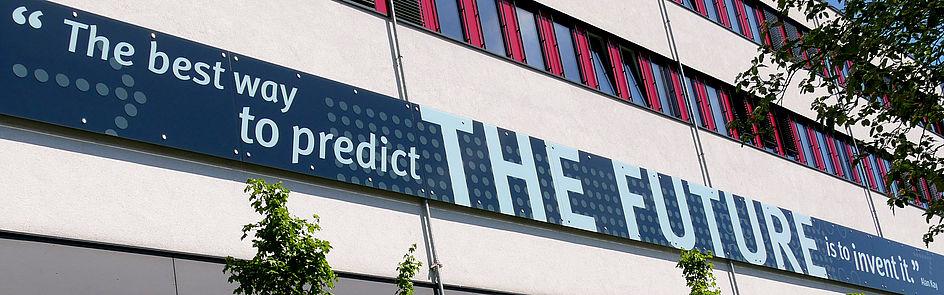 """Gebäude O (Ansicht von Osten) mit dem Zitat """"The best way to predict THE FUTURE is to invent it."""" von Alan Kay."""