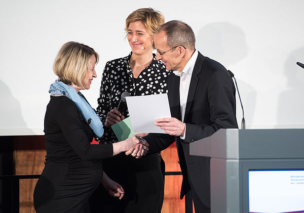Foto (Costa Belibasakis/TH Köln): Wildt-Preisverleihung durch Prof. Dr Niclas Schaper: Prof. Dr. Niclas Schaper, die Moderatorin (mittig) und eine der beiden Preisträgerinnen.