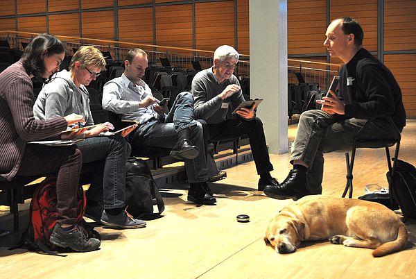 Foto (Universität Paderborn): Jürgen Fleger erläutert einigen Tagungsteilnehmern die Bedienungshilfe VoiceOver.