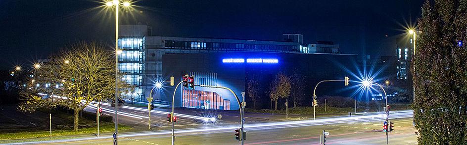 In den frühen Abendstunden leuchtet die Universität – ein Blick vom Südring auf das Hörsaal-Gebäude L.