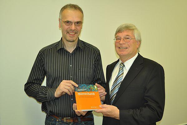 """Foto (Universität Paderborn): Prof. Dr.-Ing. Gunter Kullmer (li.) und Prof. Dr.-Ing. Hans Albert Richard mit dem neuen Fachbuch """"Biomechanik""""."""