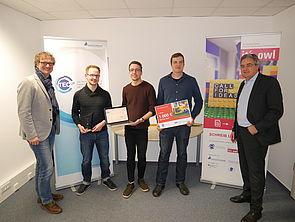 Foto (TecUP, Universität Paderborn): Zu Besuch bei dem Gewinnerteam 2016 Philipp Bednarek (2. v. l.), Christoph Bach (m.) und Marcel Hartmann (2. v. r.) – Rüdiger Kabst (l.) und Karl-Heinz Rawert (r.) freuen sich über die Fortschritte des jungen Star
