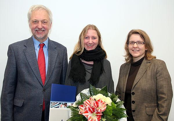 Foto (Universität Paderborn, Nina Reckendorf): Uni-Präsident Prof. Dr. Wilhelm Schäfer und Prof. Dr. Christine Silberhorn (rechts), Vizepräsidentin für Forschung und wissenschaftlichen Nachwuchs, gratulieren Dr. Charis Goer (Mitte) zu dem Stipendium.