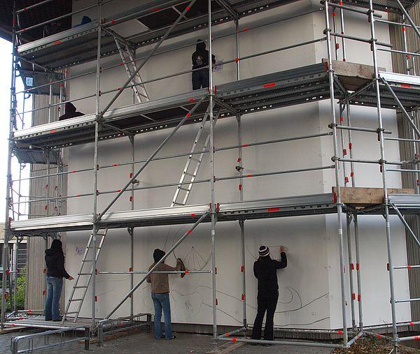 Foto (Universität Paderborn, Martin Decking): Noch ganz ohne Farben präsentierte sich die Wand des Gebäudes E bei Vorbereitungsarbeiten am 12.11.2010.