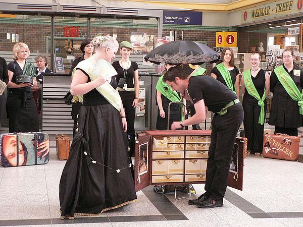 Foto: Bahnhof Weimar, Performance von Sonja Böhlen als Herzogin Anna Amalia und Mirko Winter als Kavalier zu einem Museumskoffer