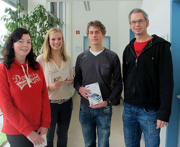 Foto (Universität Paderborn, Cinderella Schröder): Jörn Sickelmann (rechts) bei der Übergabe der Sachpreise. Die glücklichen Gewinner/innen (v. re.): Jens Beutel, Alina Jonas und Janine Hamm.