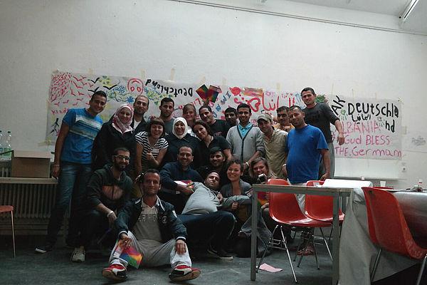 Foto (Universität Paderborn, Fach Kunst): Gruppenbild mit einigen Flüchtlingen und Helferinnen.