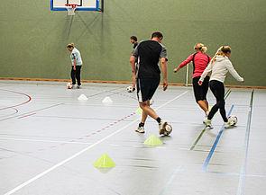 Foto (Universität Paderborn, Alena Gold): Unter Anleitung von Rene Wegs vom UFC Paderborn lernen die Teilnehmer des Workshops Futsal – eine abgemilderte Variante von Fußball, die sich gut für das Zusammenspiel von Anfängern und Profis eignet – kennen.