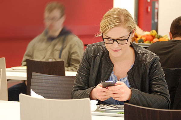 Foto (Studierendenwerk Paderborn): Studentin in der Mensa Forum des Studierendenwerks Paderborn auf dem Campus der Universität Paderborn – Mobiler Informationsabruf.