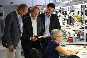 Foto: Wolfgang Kaiser (Friedr. Freek GmbH, links) zeigt Prof. Dr. Niclas Schaper und Projektmitarbeiter Julian Decius (jeweils Universität Paderborn) den Einsatzort der im Projekt StraKosphere konzipierten Kompetenzmanagementtabelle.