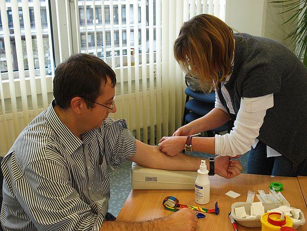 Foto (Universität Paderborn, Martin Decking): Auch Prof. Dr. Marco Platzner beteiligte sich an der Typisierungsaktion. Claudia Effgen-Lang entnahm ihm dafür 5 ml Blut, um die Gewebemerkmale in eine bundesweite Spenderdatei aufzunehmen.
