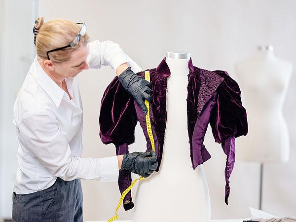 Foto (Universität Paderborn, Besim Mazhiqi): Prof. Dr. Kerstin Kraft von der Universität Paderborn untersucht historische Kleidungsstücke, um daraus Rückschlüsse auf frühere Bewegungsformen zu ziehen.