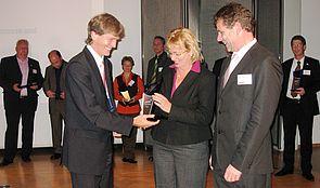 """Foto (MEIM): Auch Bettina und Bernd Langer, Gründer der BBL Software GmbH, erhielten von Uni-Präsident Prof. Dr. Nikolaus Risch als Auszeichnung das Label """"Unternehmensgründung aus der Universität Paderborn""""."""