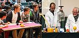 Fotos (Universität Paderborn, Adelheid Rutenburges): Gespannte Blicke eines Rateteams: Wie wird das Experiment ausgehen? Prof. i. R. Dr. Heinrich Marsmann (rechts) und Dr. Andreas Hoischen präsentieren Naturwissenschaft zum Staunen.