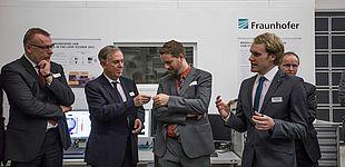Foto: Eine Station des Institutsrundgangs war der Versuchsstand für einen selbstkorrigierenen Stanzbiegeprozess. V. l. n. r.: Dr. Stefan Schwehr (paragon AG), Dr. Eduard Sailer (Miele & Cie. KG), Prof. Dr. Eric Bodden (Universität Paderborn/Fraunhofer I