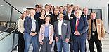 """Abbildung: Paderborner Wirtschaftspädagogen freuen sich inmitten der Projektpartner von vier Berufskollegs und der Bezirksregierung Detmold über die gelungene Auftaktveranstaltung von """"QBi"""". Links vorne: Dr. Petra Frehe, Professorin Nicole Kimmelman"""