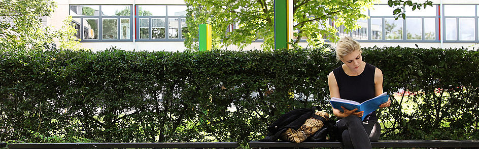 Ein Plätzchen im Schatten: Die Bänke vor dem Audimax werden bei sommerlichen Temperaturen zu gern genutzten Lernplätzen.
