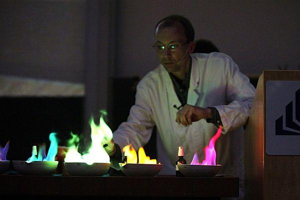 """Foto (Universität Paderborn, Adelheid Rutenburges): Farben, die im Dunkeln leuchten, zeigt Dr. Andreas Hoischen vom Department Chemie in der """"Weihnachtsvorlesung"""" am 15.12. im Audimax."""