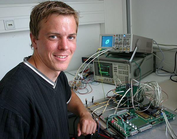 Foto (Stefan Freundlieb): Dipl.-Ing. Timo Pfau vom Institut für Elektrotechnik und Informationstechnik der Universität Paderborn vor einigen elektrischen Geräten des komplizierten Empfängers.