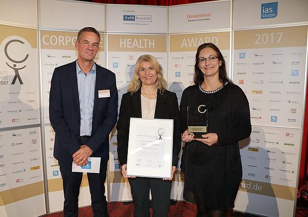 Foto (EuPD Research Sustainable Management GmbH): (v. l.) Thomas Holm, Leiter des Gesundheitsmanagements bei der Techniker Krankenkasse, überreichte den Preis an Diana Riedel und Sandra Bischof.