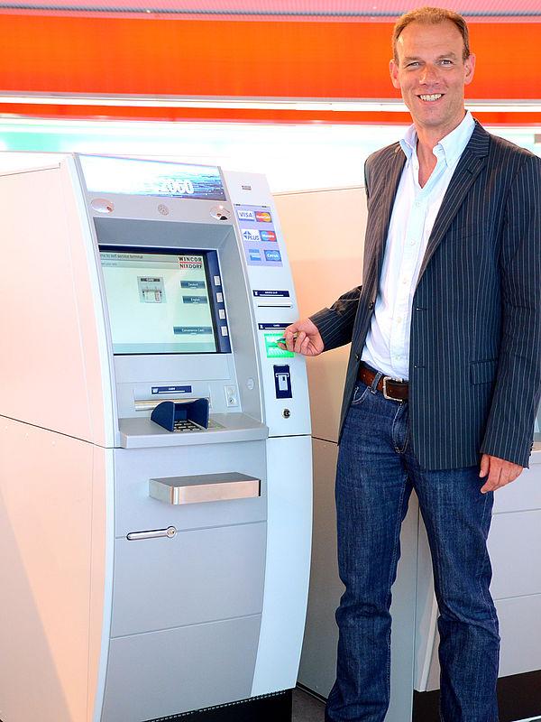 Foto (Stefan Pföhler und Simone Rudolph): Prof. Dr. Johannes Blömer vor einem Geldausgabeautomaten des Projektpartners Wincor Nixdorf.