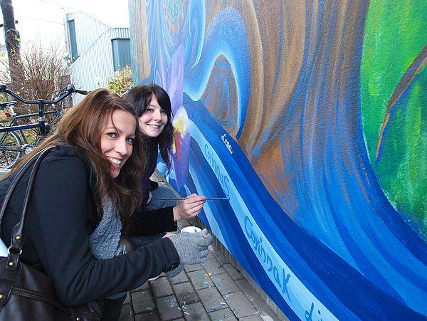 Foto (Universität Paderborn, Martin Decking): Corinna Seifert und Corinna Kunz (v.l.) studieren Kunst sowie Spanisch bzw. Deutsch auf Lehramt im 3. Semester. Hier signieren sie das gemeinsame Kunstwerk.