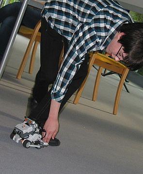 Foto: Daniel stellt seinen selbstprogrammierten Roboter vor.