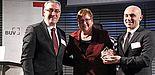 Foto (Raynet GmbH), v. li.: Der Präsident des BUV, Osman Kimil, und die Parlamentarische Staatssekretärin beim Bundesminister für Wirtschaft und Energie, Iris Gleicke, gratulieren Ragip Aydin.