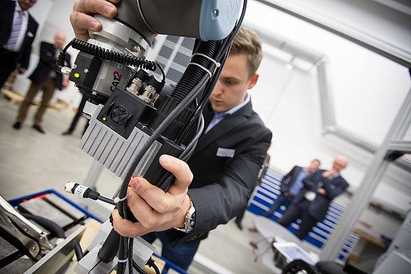 Stefan Schütz (Fraunhofer IEM) zeigt die Zusammenarbeit mit einem kollaborativen Roboter. Foto: David Gense
