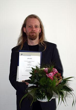 """Foto (Universität Paderborn, Bianca Oldekamp): Dr. Adrian Keller nahm den Forschungspreis 2014 für das Projekt """"Selbstassemblierte DNA-Nanodrähte für zukünftige Informationstechnologie"""" entgegen."""
